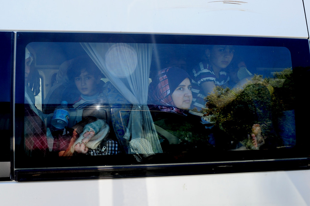. Syrian refugees leave on a bus on June 8, 2011 the Yayladagi Turkish Red Crescent camp near the Turkish city of Hatay. Turkey will not close its doors to hundreds of refugees fleeing repression in Syria, Prime Minister Recep Tayyip Erdogan said on June 8, voicing concern at growing unrest across the border. Some 120 Syrian refugees crossed over into Turkey late on June 7. Another 160 followed on June 8, bringing to at least 550 the number to enter the country in recent days. MUSTAFA OZER/AFP/Getty Images