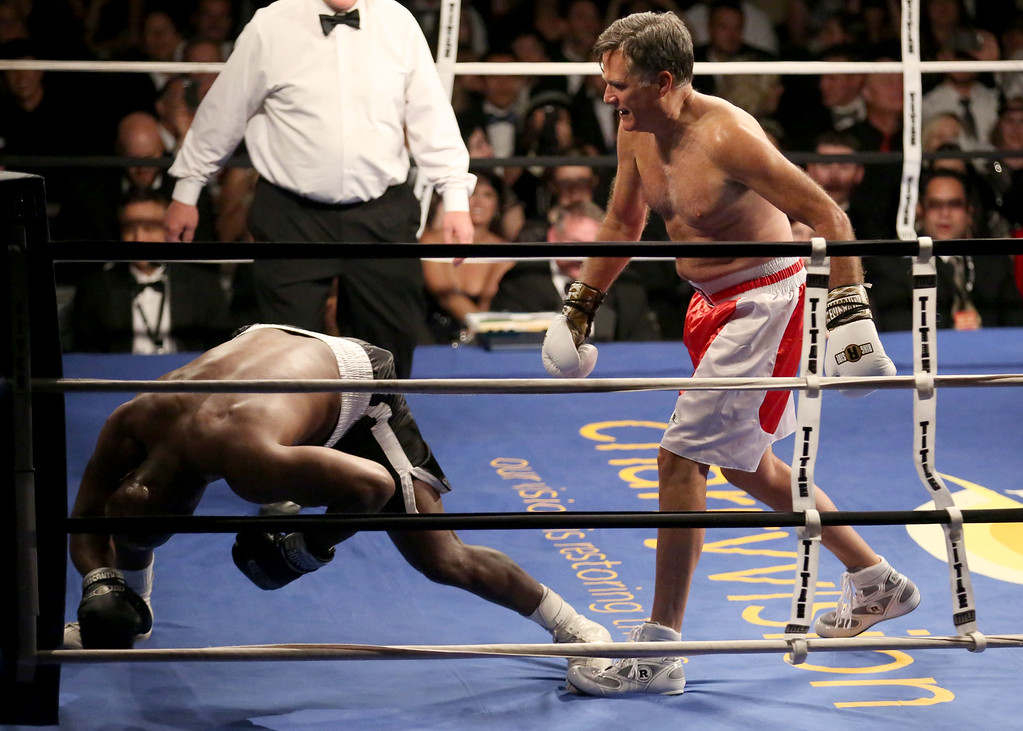 . Former Republican presidential candidate Mitt Romney knocks five-time heavyweight boxing champion Evander Holyfield, left, to the mat during a charity fight night event Friday, May 15, 2015, in Salt Lake City. The black-tie event raised money for the Utah-based organization CharityVision, which helps doctors in developing countries perform surgeries to restore vision in people with curable blindness. (Kristin Murphy/Deseret News via AP)