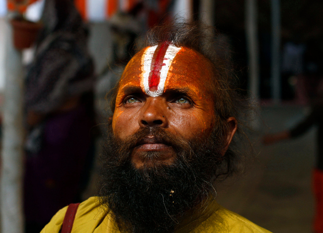 . A Hindu holy man pauses as he returns after taking part in a community feast at the Ashram of Swami Ramanand Das at Sangam, the confluence of the Ganges and Yamuna River during the Maha Kumbh festival, in Allahabad, India, Wednesday, Feb. 20, 2013. Millions of Hindu pilgrims have been attending the Maha Kumbh festival, which is one of the world\'s largest religious gatherings that lasts 55 days and falls every 12 years. (AP Photo/ Rajesh Kumar Singh)