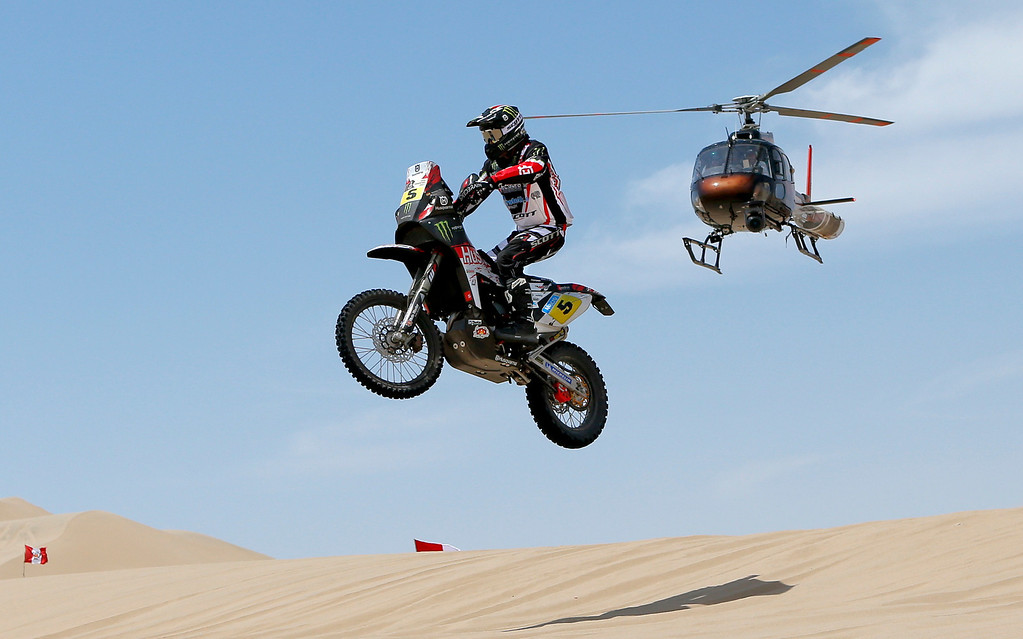 . Husqvarna rider Joan Barreda Bort of Spain competes in the stage one as a helicopter flies above during the 2013 Dakar Rally between Lima and Pisco, Peru, Saturday, Jan. 5, 2013. The race finishes in Santiago, Chile, on Jan. 20. (AP Photo/Victor R. Caivano)