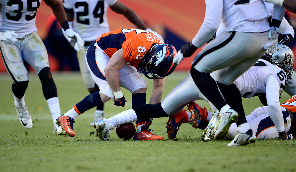. DENVER, CO - DECEMBER 28: C.J. Anderson (22) of the Denver Broncos fumbles the ball in the second quarter.  The ball was recovered by Wes Welker (83) of the Denver Broncos.  The Denver Broncos played the Oakland Raiders at Sports Authority Field at Mile High in Denver on December, 28 2014. (Photo by Joe Amon/The Denver Post)