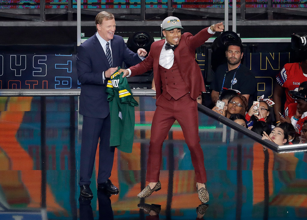 . Commissioner Roger Goodell, left, watches as Louisville\'s Jaire Alexander celebrates after being selected by the Green Bay Packers during the first round of the NFL football draft, Thursday, April 26, 2018, in Arlington, Texas. (AP Photo/Eric Gay)