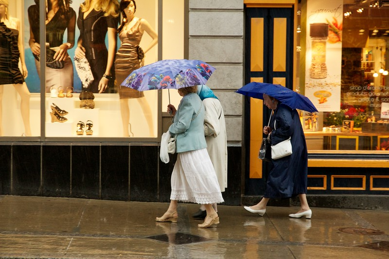 Three women with umbrellas on a rainy day. Rue Saint-Jean, Quebec City, Canada.