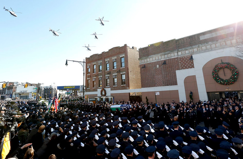 . Law enforcement helicopters fly over Christ Tabernacle Church, where the casket of New York City police officer Rafael Ramos is carried by pallbearers, center, in the Glendale section of Queens, Saturday, Dec. 27, 2014, in New York. Ramos and his partner, officer Wenjian Liu, were killed Dec. 20 as they sat in their patrol car on a Brooklyn street. The shooter, Ismaaiyl Brinsley, later killed himself. (AP Photo/Julio Cortez)