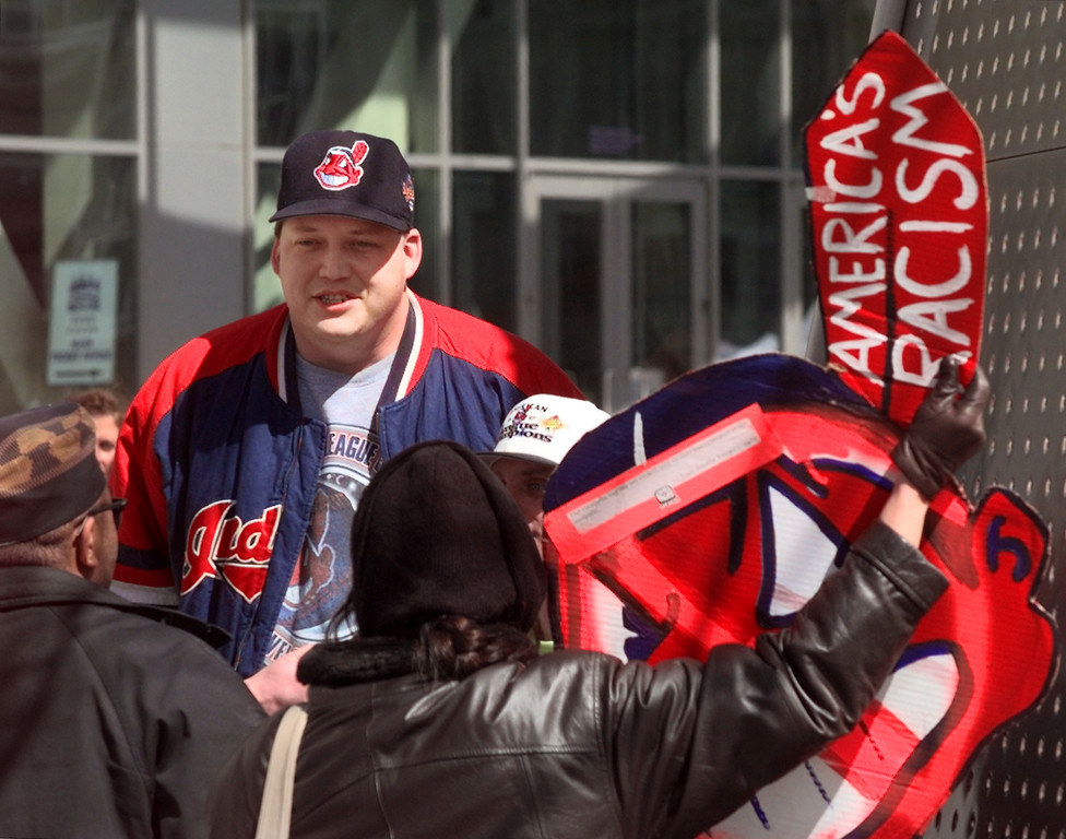 . A fan wearing a Chief Wahoo cap talks with protesters demonstrating against the Cleveland Indians mascot outside Jacobs Field before the team\'s home opener April 10, 1998, in Cleveland. (AP Photo/Mark Duncan, File)