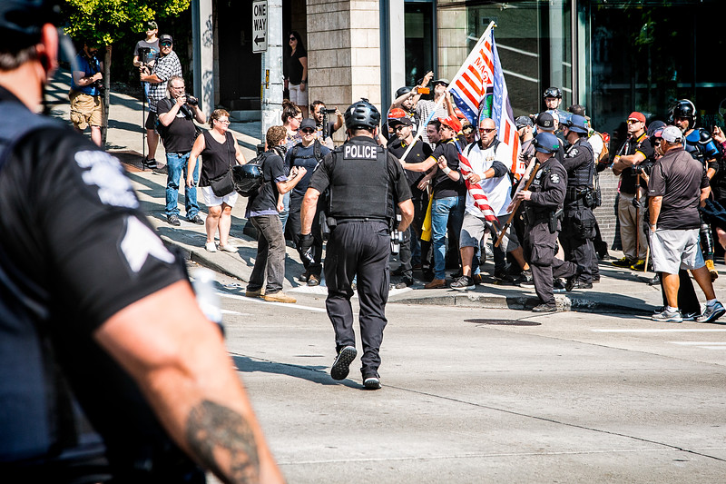 """A bit of a melee begins to break out at 4th Ave and Cherry St between a single anti-fascist with his fists up and someone from the """"Liberty or Death"""" crowd. Although I took several shots, I never saw what transpired; the police were in the way of my shots. However, A Trump supporter was injured and the anti-fascist was handcuffed and taken away."""