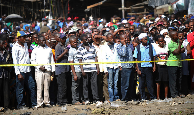 . Onlookers gather behind police tape at the site where two blasts detonated, one in a mini-van used for public transportation, in a market area of Nairobi, Kenya, Friday, May 16, 2014. Two blasts hit Kenya\'s capital on Friday, killing a number of people and injuring many more, in what appeared to be the latest in a string of increasingly frequent terror attacks. (AP Photo)