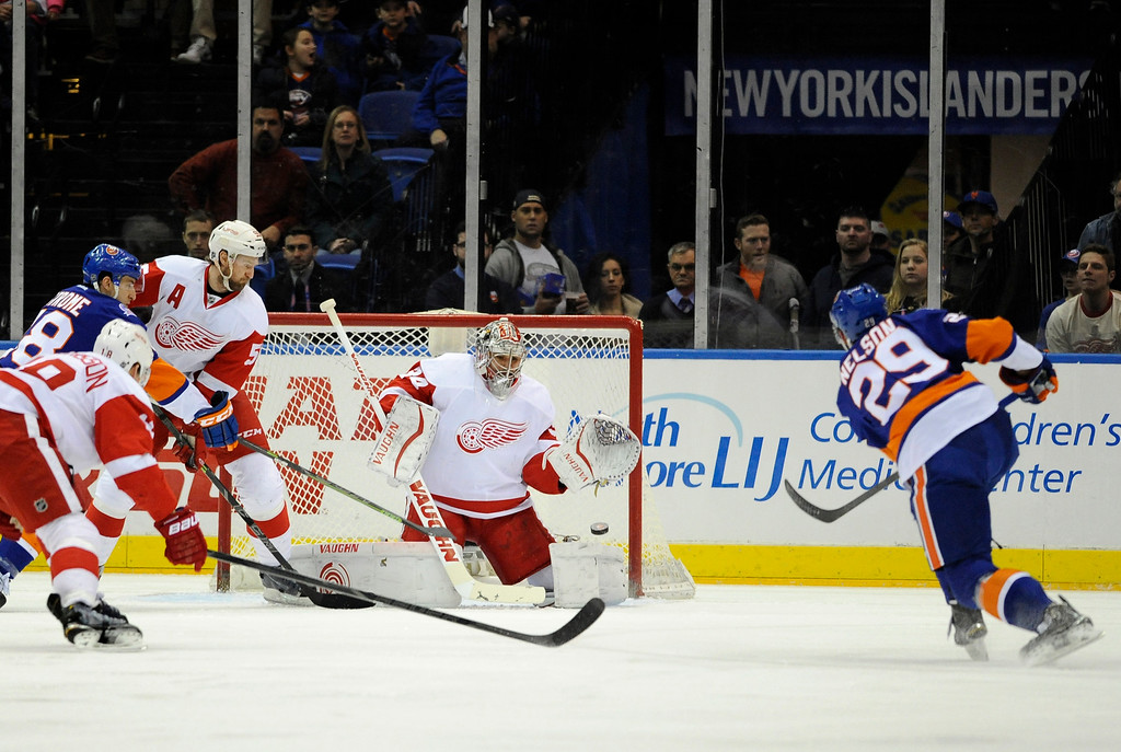 . New York Islanders center Brock Nelson (29) shoots the puck past Detroit Red Wings goalie Petr Mrazek (34) for a goal as Red Wings center Joakim Andersson (18) and defenseman Niklas Kronwall (55) defend against Islanders center Ryan Strome (18) during the first period of an NHL hockey game Sunday, March 29, 2015, in Uniondale, N.Y. (AP Photo/Kathy Kmonicek)