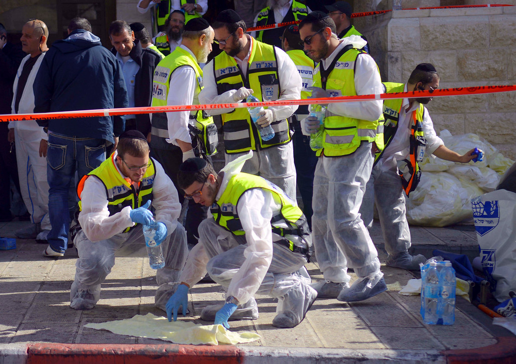. Paramedics wipe the blood from pavement outside a synagogue after a shooting attack in Jerusalem, Tuesday, Nov. 18, 2014. Two Palestinian cousins stormed a Jerusalem synagogue on Tuesday, attacking worshippers with meat cleavers and a gun during morning prayers and killing four people in the city\'s bloodiest attack in years. The attackers were killed in a shootout with police. (AP Photo/Mahmoud Illean)
