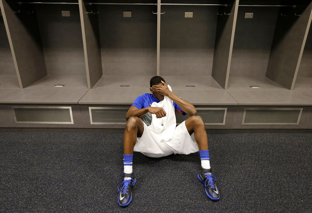. Florida forward Dorian Finney-Smith reacts in the locker room after an NCAA Final Four tournament college basketball semifinal game against Connecticut Saturday, April 5, 2014, in Arlington, Texas.  Connecticut won 63-53(AP Photo/Eric Gay)