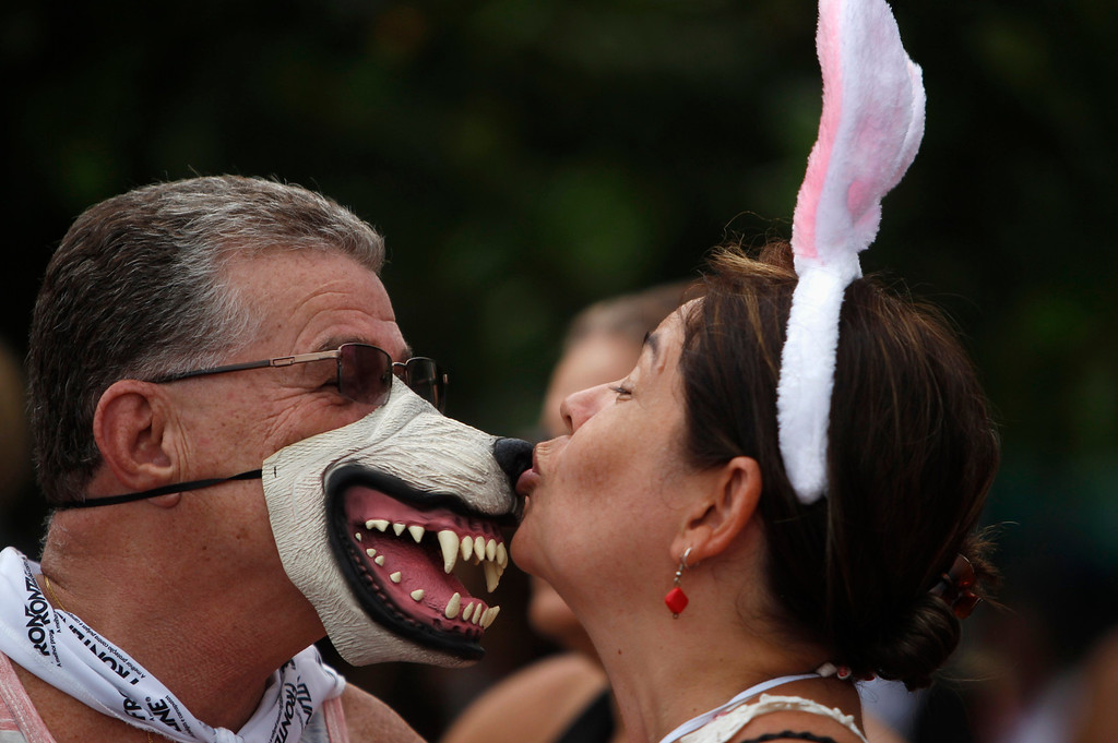 ". A couple kiss each other at the ""Blocao\"" dog carnival parade during pre-carnival festivities along Copacabana beach in Rio de Janeiro February 3, 2013.  REUTERS/Pilar Olivares"