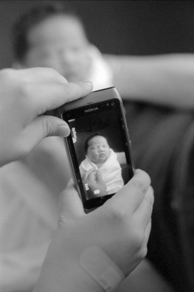 A story of 3 generations. Mommy is taking a photo on the phone, while she is in Grandma's hands.