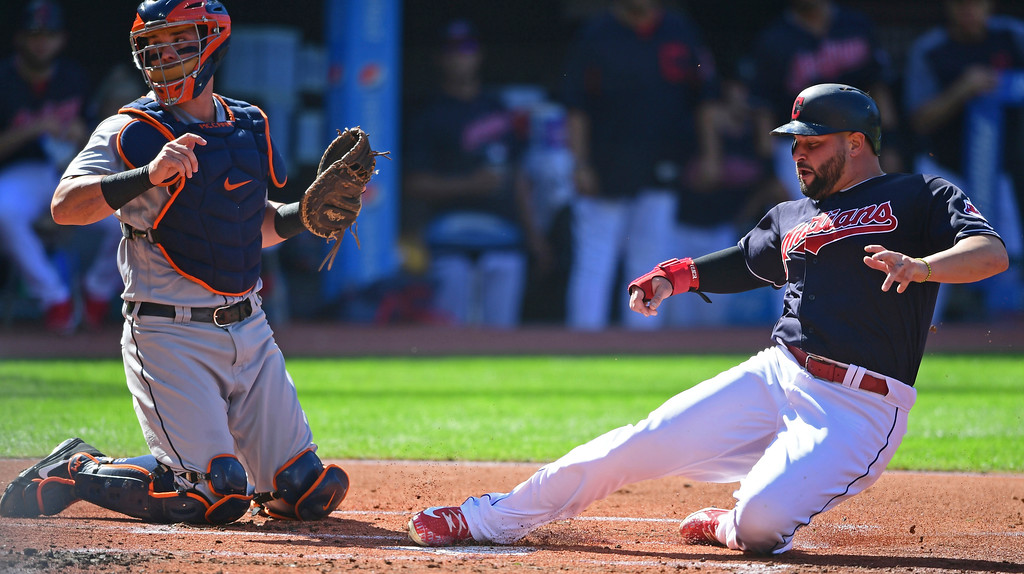 . Cleveland Indians\' Yonder Alonso slides safely into home plate as Detroit Tigers catcher James McCann looks for the ball in the first inning of a baseball game, Saturday, Sept.15, 2018, in Cleveland. (AP Photo/David Dermer)