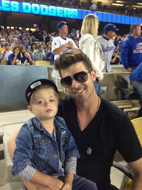 . In this handout photo provided by the Los Angeles Dodgers, Robin Thicke (R) poses for a photo with son Julian Fuego Thicke at the New York Mets v Los Angeles Dodgers game at Dodger Stadium on August 14, 2013 in Los Angeles, California. (Photo by Los Angeles Dodgers via Getty Images)
