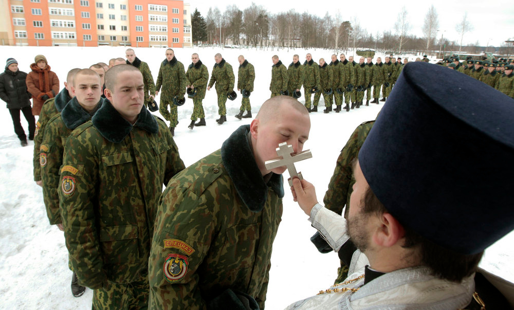 . Servicemen of the Belarussian Interior Ministry\'s special unit queue up to kiss an Orthodox Cross after a service at a military base in Minsk January 7, 2013. Most Orthodox Christians celebrate Christmas according to the Julian calendar on January 7, two weeks after most western Christian churches that abide by the Gregorian calendar.   REUTERS/Vasily Fedosenko