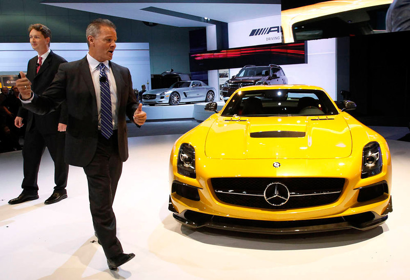 . Stephen Cannon, President and CEO of Mercedes-Benz USA, (2nd L) walks around a 2013 Mercedes-Benz SLS AMG Black Series gullwing at the 2012 Los Angeles Auto Show in Los Angeles, California November 28, 2012.   REUTERS/Mario Anzuoni
