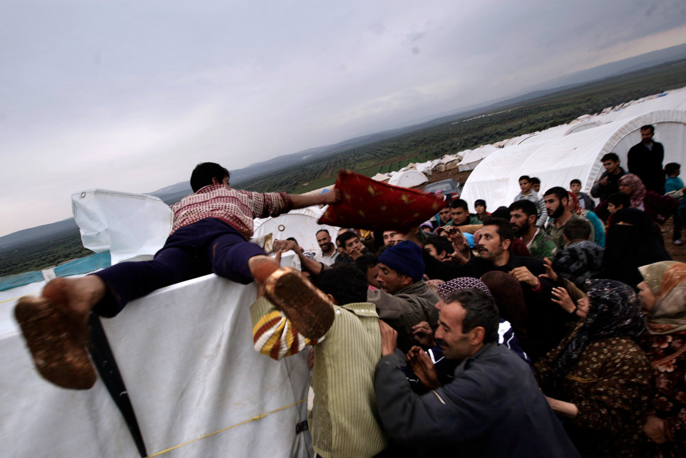 . In this Monday, Dec. 10, 2012, photo, Syrians who fled their homes struggle to get pillows and blankets distributed at a camp for displaced Syrians, in the village of Atmeh, Syria. This tent camp sheltering some of the hundreds of thousands of Syrians uprooted by the country\'s brutal civil war has lost the race against winter: the ground under white tents is soaked in mud, rain water seeps into thin mattresses and volunteer doctors routinely run out of medicine for coughing, runny-nosed children. (AP Photo/Muhammed Muheisen)