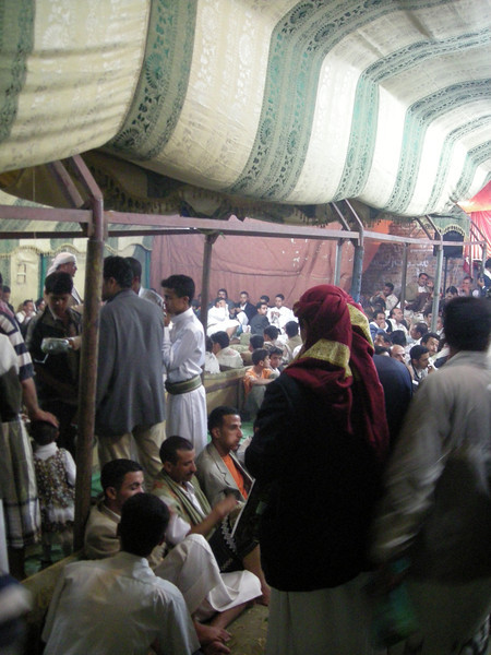 the men's guest tent set up in the street, old Sana'a,  guests enjoy relaxing and chewing qat.