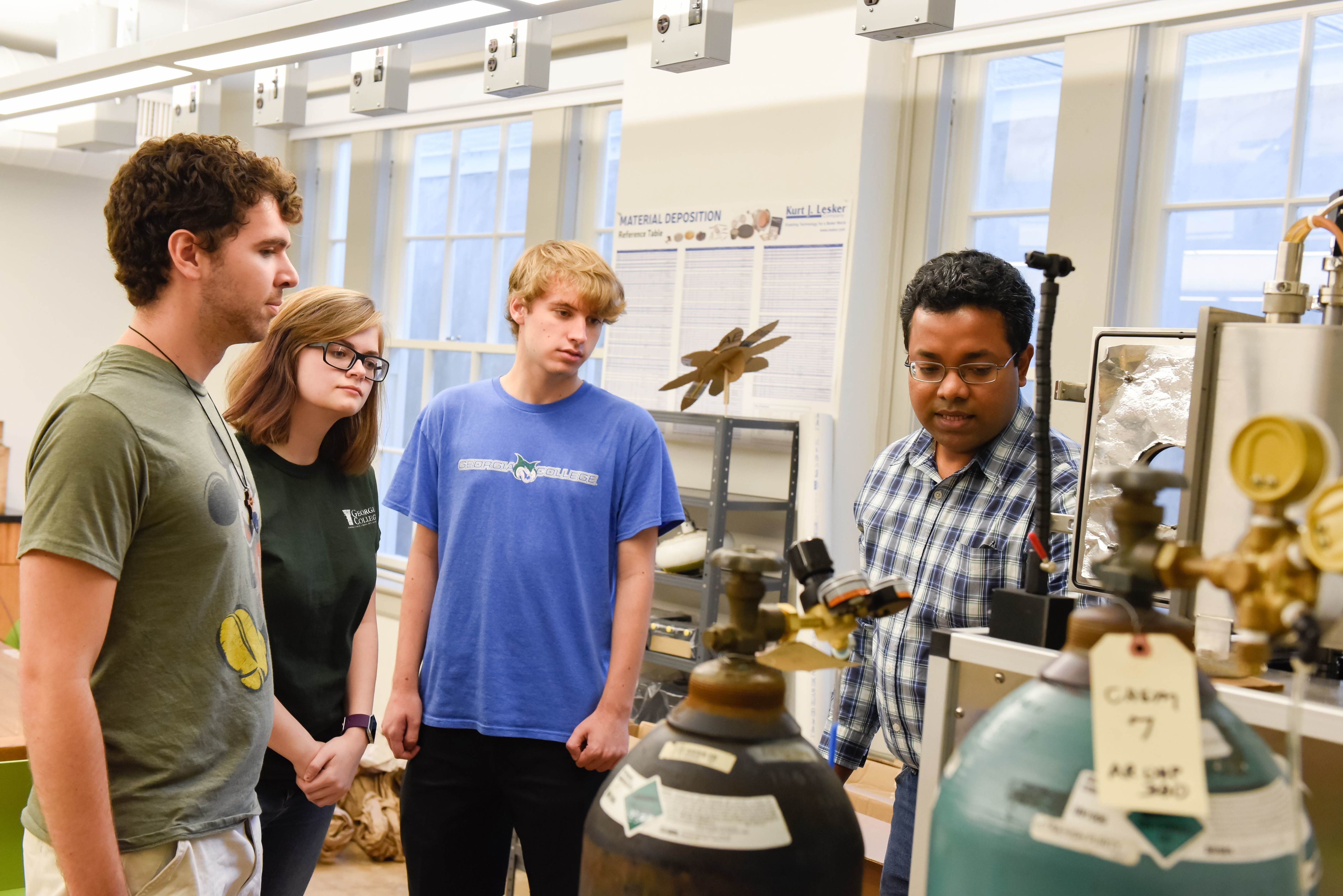 Dr. Hasitha Mahabaduge, right, in the physics lab with students.