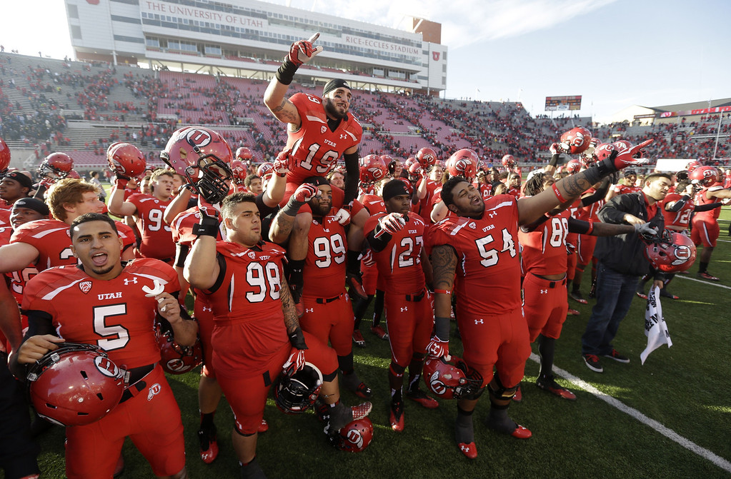. Utah players celebrate at the end of their NCAA college football game against Colorado Saturday, Nov. 30, 2013, in Salt Lake City. Utah won 24-17. (AP Photo/Rick Bowmer)