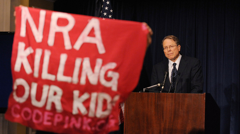 . A protester holds up a sign as Wayne LaPierre, executive vice-president of the National Rifle Association of America (NRA), speaks at a news conference at the Willard Hotel, December 21, 2012 in Washington, DC. The nation\'s largest gun lobby called Friday for Congress to require armed security guards in every school, saying it would help prevent such acts of mass violence from happening again. (Olivier Douliery/Abaca Press/MCT)