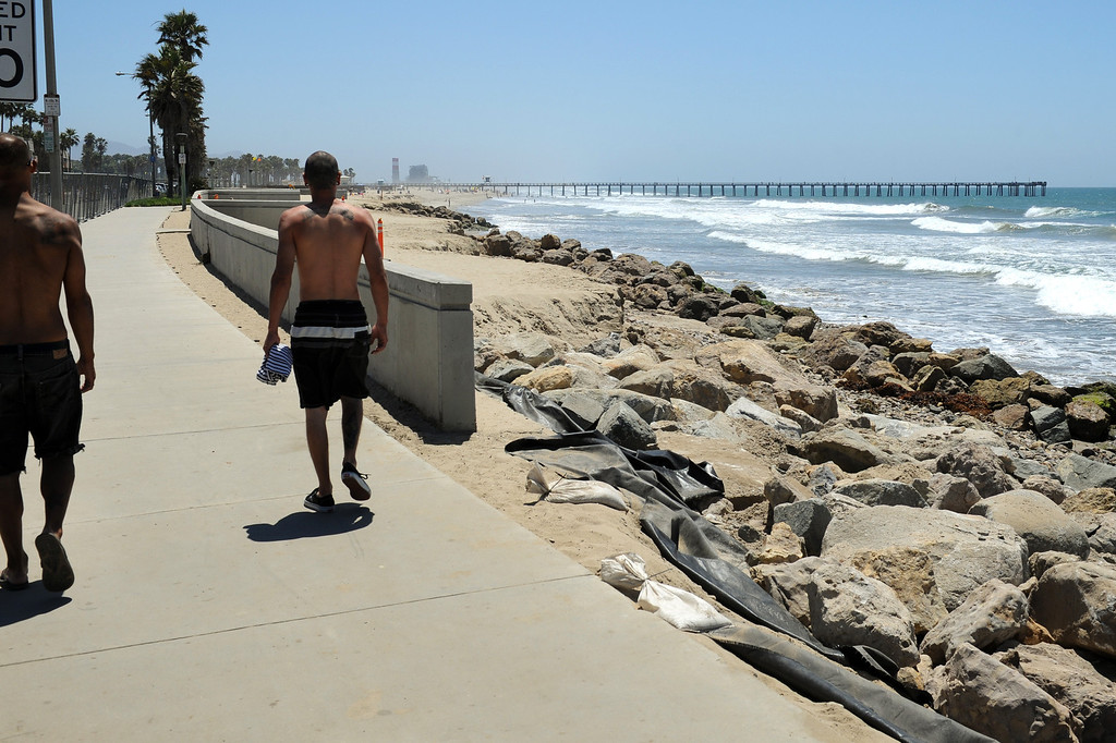 . People walk along a fence-off sidewalk at Hueneme Beach where sand has washed away during the past several months, Monday, July 15, 2013. (Michael Owen Baker/L.A. Daily News)