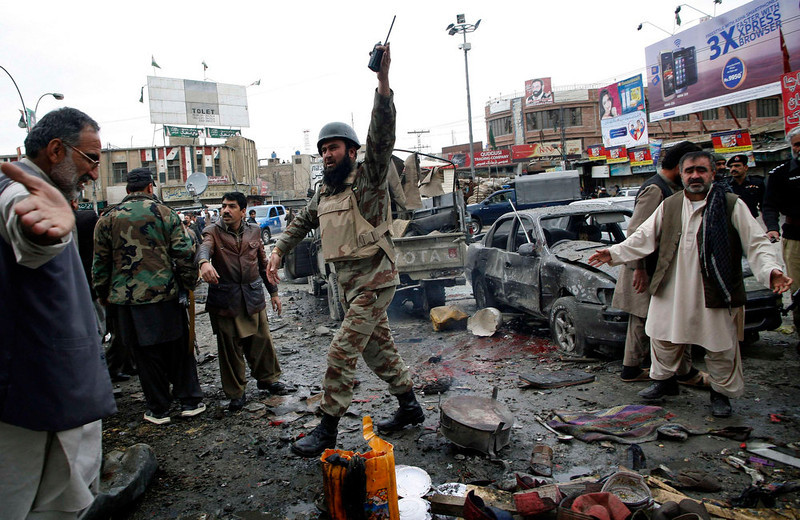 . A paramilitary soldier reacts as he asks civilian to leave the scene of a bomb explosion in Quetta January 10, 2013. At least 12 people, including a child and two security personnel, were killed and 30 others injured in a blast that took place near Quetta\'s Bacha Khan chowk on Thursday, local media said. REUTERS/Naseer Ahmed