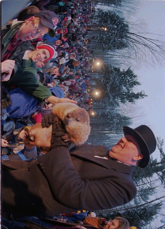 . Punxsutawney Phil\'s handler Bill Deeley, right, holds Phil out to some of the over 10,000 faithful who braved single digit temperatures on Gobbler\'s Knob in Punxsutawney, Pa., Friday morning Feb. 2, 1996 to hear the weather prognostication of the famous groundhog. Phil saw his shadow and forecast six more weeks of winter. (AP Photo/Gene J. Puskar)