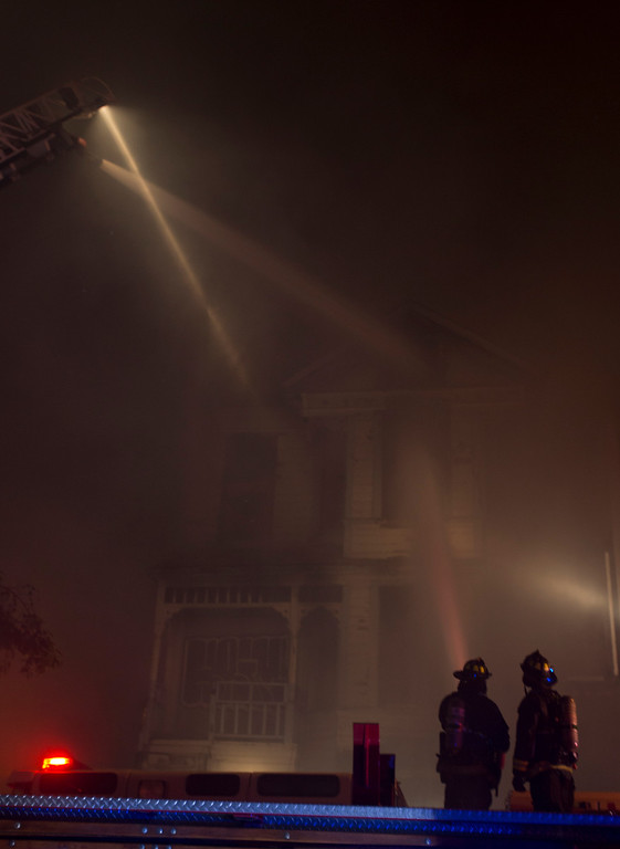 . Firefighters watch as a snorkel pours water on the flames from a fire inside a vacant, wood-framed house on Harrison Street near 7th Street, Wednesday, Jan. 23, 2013 in Oakland, Calif. The building, which fire investigators said was built in 1896, caught fire when squatters inside it tried to cook food over an open flame. (D. Ross Cameron/Staff)