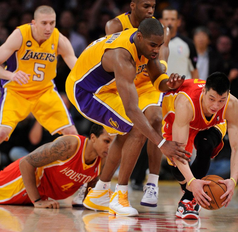 . Rockets#7 Jeremy Lin picks up a loose ball before Lakers#4 Antawn Jamison can get to it. The Lakers defeated the Houston Rockets in overtime 99-95 in the final home game of the year at Staples Center in Los Angeles, CA 4/17/2013(John McCoy/Staff Photographer