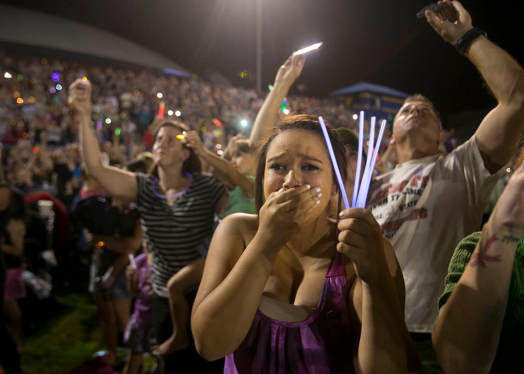 . Keira Ewing, 15, of Prescott Valley, Ariz. cries during a vigil for the 19 firefighters killed battling the Yarnell Hill Fire, on the football field at Prescott High School in Prescott, Ariz. on Tuesday, July 2, 2013. (AP Photo/The Arizona Republic, David Wallace)