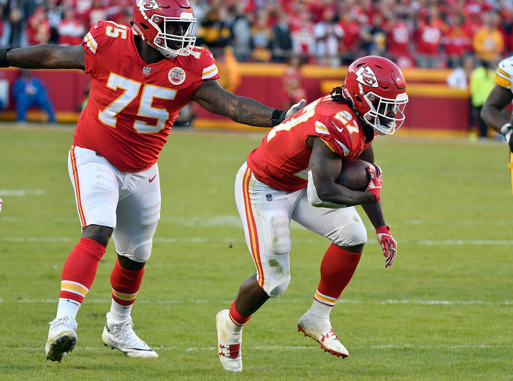 . Kansas City Chiefs running back Kareem Hunt (27) runs in front of offensive lineman Cameron Erving (75) during the second half of an NFL football game against the Pittsburgh Steelers in Kansas City, Mo., Sunday, Oct. 15, 2017. (AP Photo/Ed Zurga)