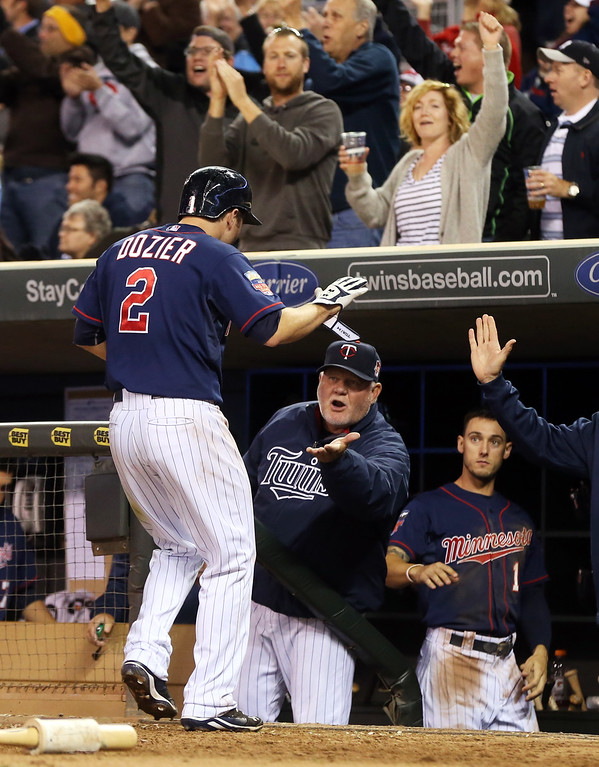 . Minnesota Twins manager Ron Gardenhire celebrates with Brian Dozier after he scored on a two-run, game-tying single by Joe Mauer off Detroit Tigers pitcher Phil Coke in the eighth inning of a baseball game, Monday, Sept. 15, 2014, in Minneapolis. The Tigers won 8-6. (AP Photo/Jim Mone)