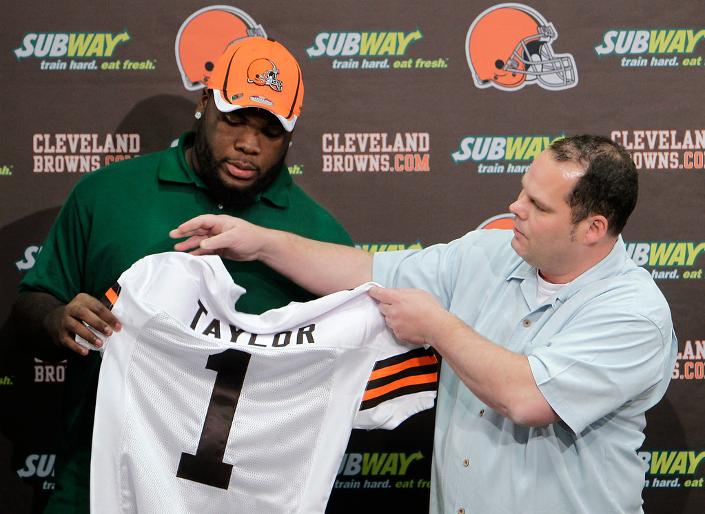. Cleveland Browns general manager Tom Heckert, right, presents a jersey to first round-draft pick Phillip Taylor during an NFL football news confernce at the team\'s headquarters in Berea, Ohio Friday, April 29, 2011. The Browns took the Baylor defensive tackle with the 21st overall pick Thursday night. (AP Photo/Mark Duncan)