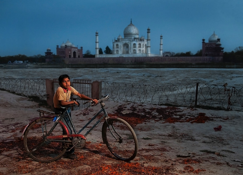 Viewed from the other side of the Jamuna river away from the noisy crowds the Taj Mahal regains its romantic beauty. A local boy, lit by the warm light of a single street lamp takes a rest before heading back to his village.