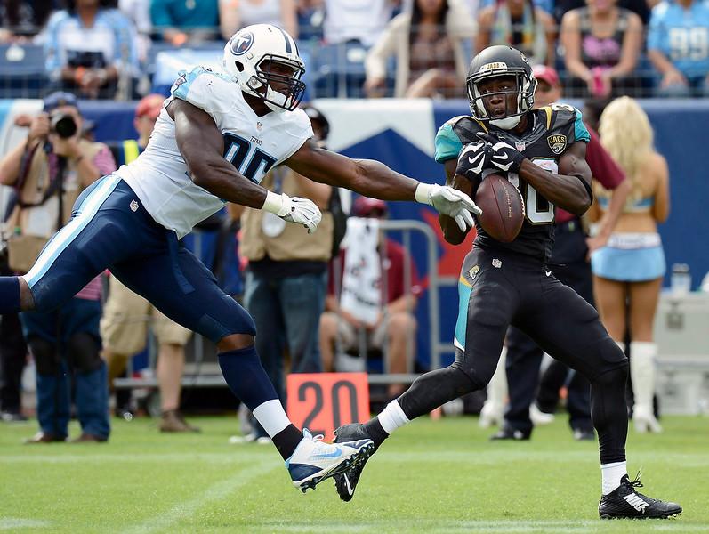 . Tennessee Titans linebacker Kamerion Wimbley (95) breaks up a pass intended for Jacksonville Jaguars running back Jordan Todman, right, in the third quarter of an NFL football game Sunday, Oct. 12, 2014, in Nashville, Tenn. (AP Photo/Mark Zaleski)
