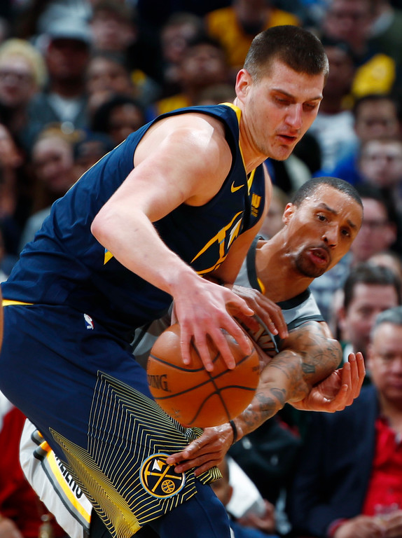 . Cleveland Cavaliers guard George Hill, back, tries to steal a pass intended for Denver Nuggets center Nikola Jokic during the first half of an NBA basketball game Wednesday, March 7, 2018, in Denver. (AP Photo/David Zalubowski)