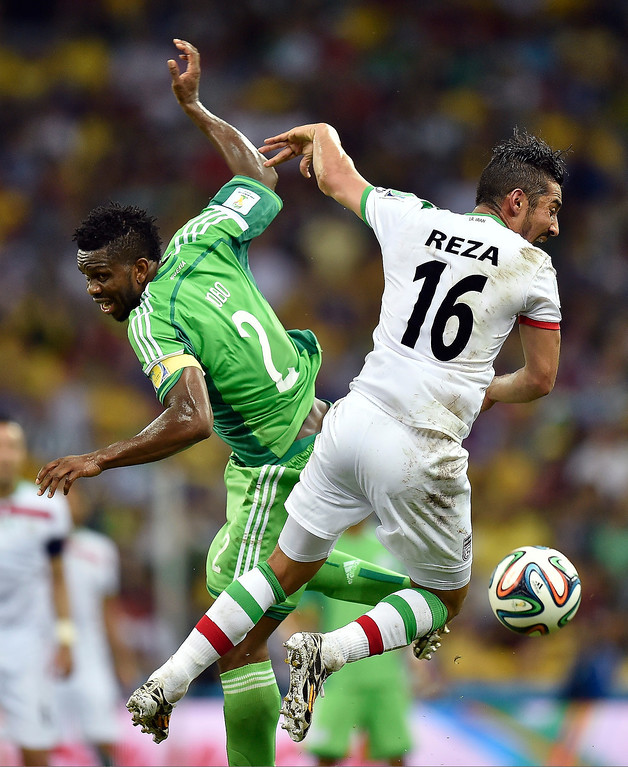. Nigeria\'s Joseph Yobo, left, challenges Iran\'s Reza Ghoochannejhad during the group F World Cup soccer match between Iran and Nigeria at the Arena da Baixada in Curitiba, Brazil, Monday, June 16, 2014.  (AP Photo/Martin Meissner)