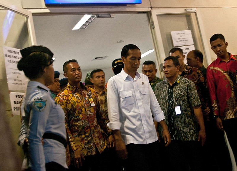 . Indonesian President Joko Widodo (C) leaves after meeting with family members of passengers onboard the missing Malaysian air carrier AirAsia flight QZ8501, at the Juanda International Airport in Surabaya on December 30, 2014.   The hunt for a missing AirAsia passenger plane appeared at an end December 30 as wreckage and bodies were spotted at sea off Indonesia, prompting raw scenes of emotion from sobbing relatives of the 162 people aboard.   JUNI KRISWANTO/AFP/Getty Images