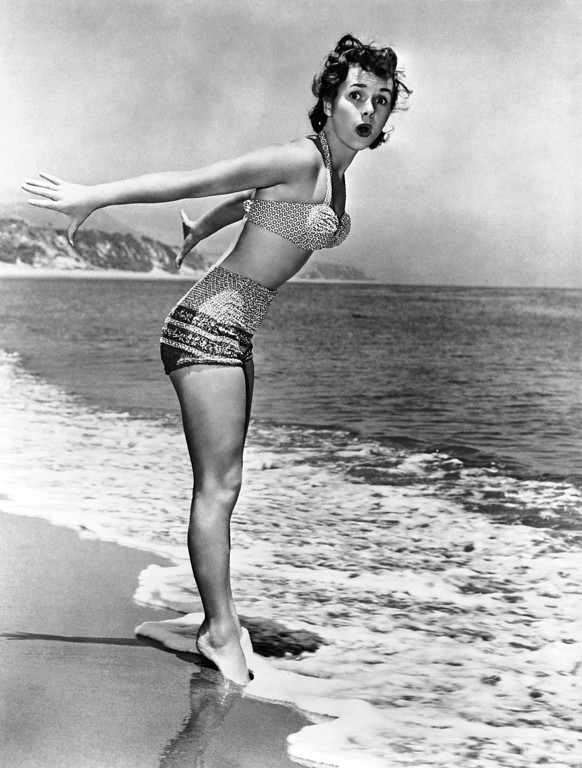 . In this photo provided by Metro-Goldwyn-Mayer, actress Debbie Reynolds, musical star in Hollywood,  decides to take a dip in the Pacific ocean on her day off from studio work, Sept. 21, 1952. The water was cold, and she quickly changed her mind. (AP Photo/MGM)
