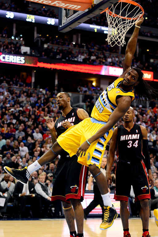 . Kenneth Faried (35) of the Denver Nuggets hangs on the rim after dunking as the Miami Heat defense looks on during the first half of action.    (Photo by AAron Ontiveroz/The Denver Post)