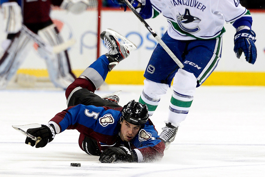 . DENVER, CO - MARCH 24: Maxim Lapierre (40) of the Vancouver Canucks sends Shane O\'Brien (5) of the Colorado Avalanche to the ice during the third period of action. The Colorado Avalanche lost to the Vancouver Canucks 3-2 at the Pepsi Center. (Photo by AAron Ontiveroz/The Denver Post)