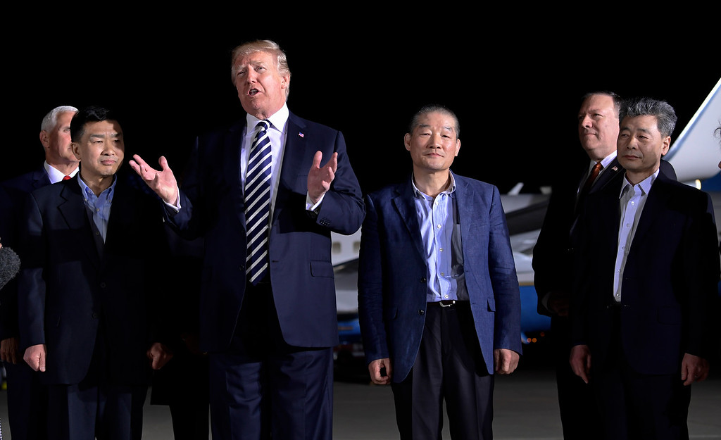 . President Donald Trump speaks as he stands with Tony Kim, second left, Kim Dong Chul, center right, and Kim Hak Song, right, three Americans detained in North Korea for more than a year after they arrived at Andrews Air Force Base in Md., Thursday, May 10, 2018. Vice President Mike Pence, left, and Secretary of State Mike Pompeo, second from right, listen. (AP Photo/Susan Walsh)