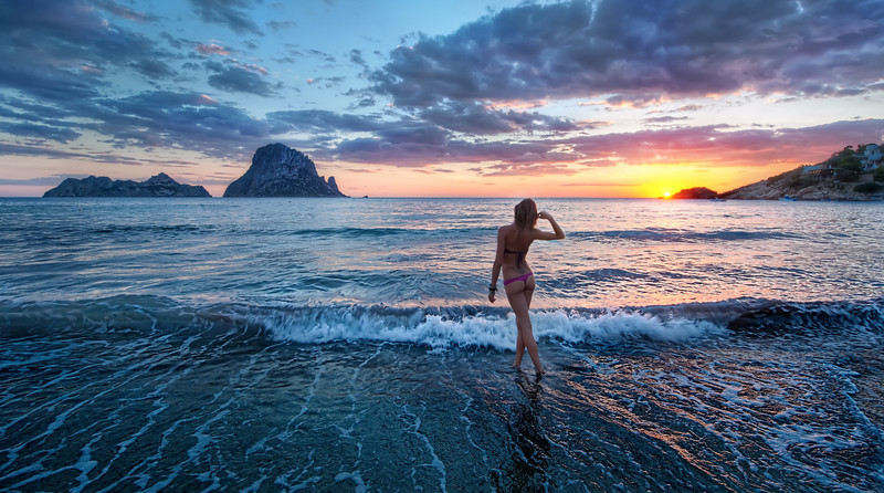 "Sunset in Ibiza Ibiza is a fabulous island off the coast of Spain that is the ""in"" destination for all the Euros that like to get trashed, party, dress in white, do medium-level-drugs, and stay on the beach without many clothes.I saw this girl bouncing around and very happy about something, so I went over and said hello, introducing myself.  She didn't speak much English, but I managed to ask her if I could take a photo of her.  She enthusiastically said yes, and I explained the sitch as we walked over to the water, mostly using interpretive dance to span the language gap.  She was Italian and her name was Wendy.  I think that is a strange name for an Italian, but I didn't question it.  Anyway, I asked her just to walk off into the ocean and I would take a photo.  She did just that, and I grabbed this shot just as the sun was dipping below the horizon.- Trey RatcliffThe rest of this entry resides here at stuckincustoms.com."