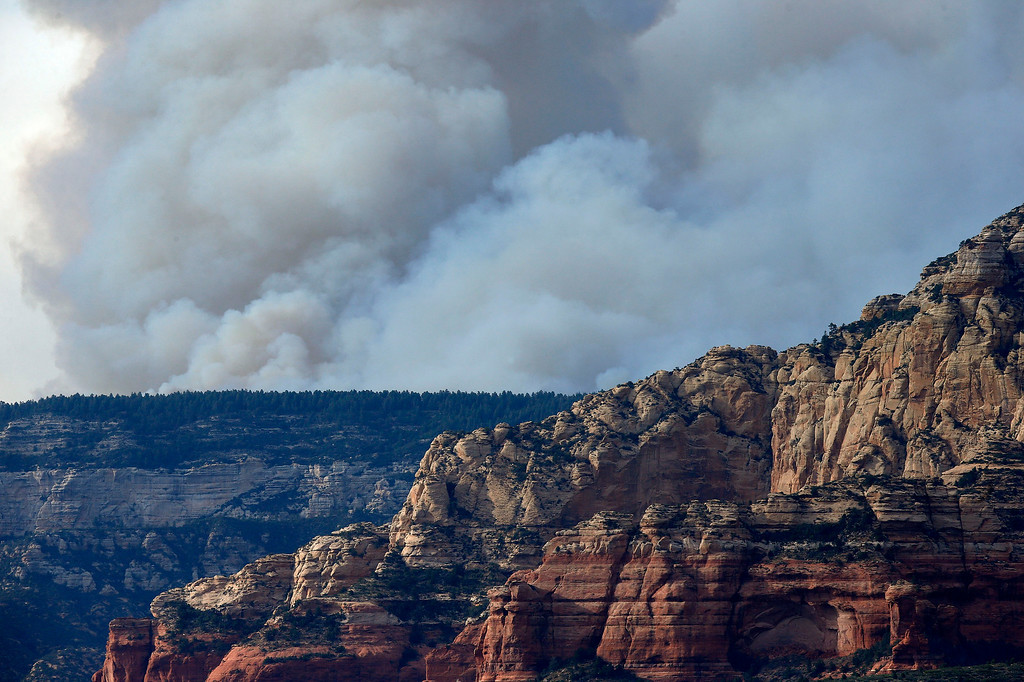 . Smoke from the Slide Fire fills the sky as it burns up Oak Creek Canyon on Thursday, May 22, 2014, in Sedona, Ariz.  The fire has burned approximately 4,800 acres. (AP Photo/Ross D. Franklin)