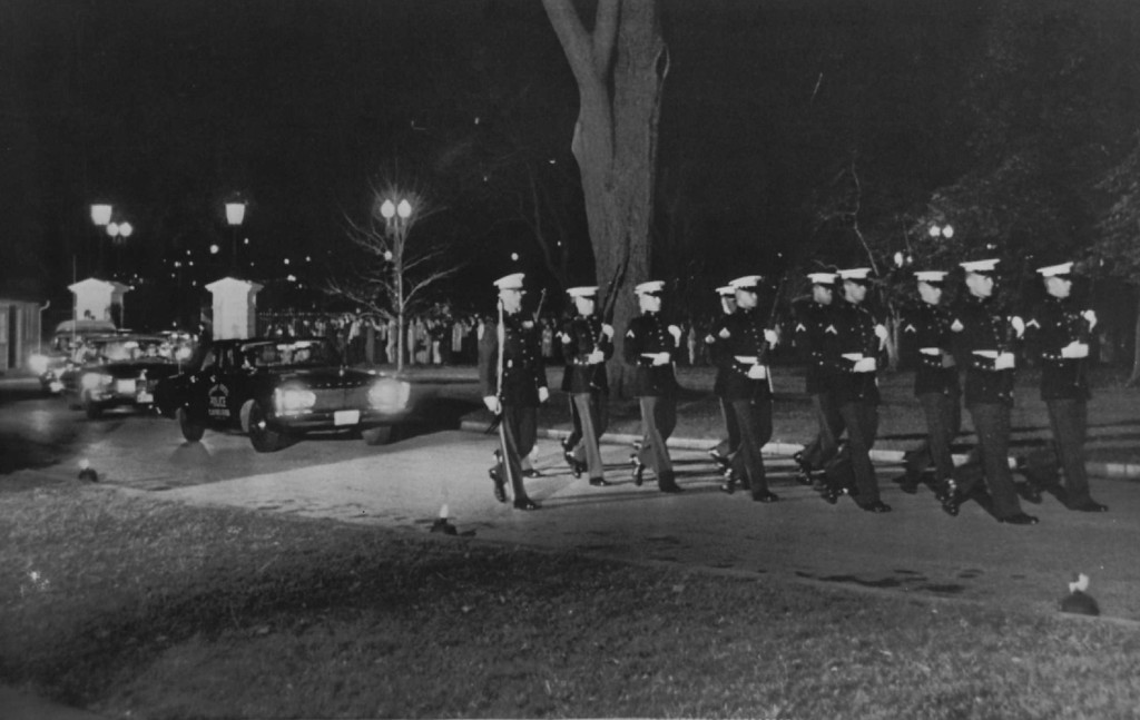 . An honor guard of Marines walks the driveway leading to the White House from Pennsylvania Avenue as Kennedy\'s body is taken to the mansion Nov. 24, 1963.