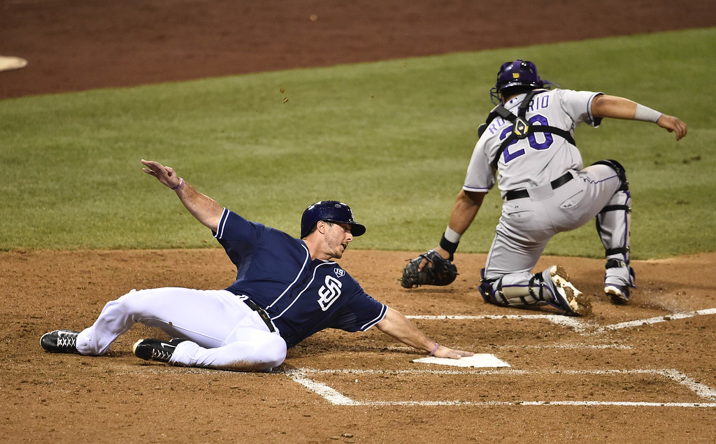 . SAN DIEGO, CA - SEPTEMBER 23:  Tommy Medica #14 of the San Diego Padres scores ahead of the throw to Wilin Rosario #20 of the Colorado Rockies during the sixth inning of a baseball game at Petco Park September, 23, 2014 in San Diego, California.  (Photo by Denis Poroy/Getty Images)