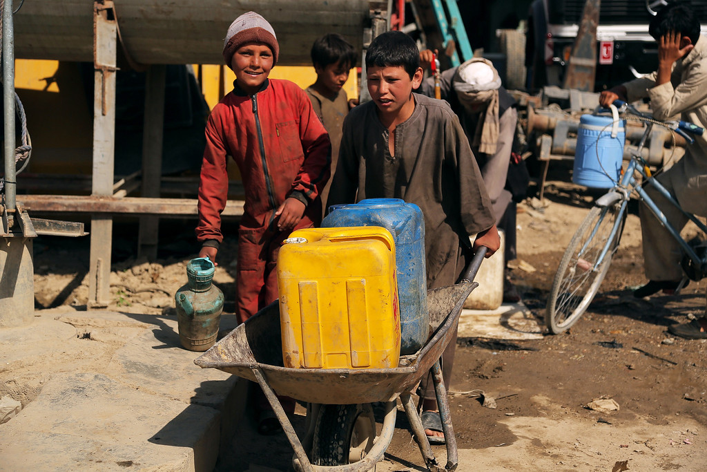 . Afghan child labourers carry water at a mechanics shop in Ghazni city, during Children\'s Day on June 1, 2013. Tens of thousands of children in Afghanistan, driven by poverty, work on the streets of the war-torn country\'s cities and often fall prey to Taliban bombings and other violence, as well as abuse. RAHMATULLAH ALIZADA/AFP/Getty Images