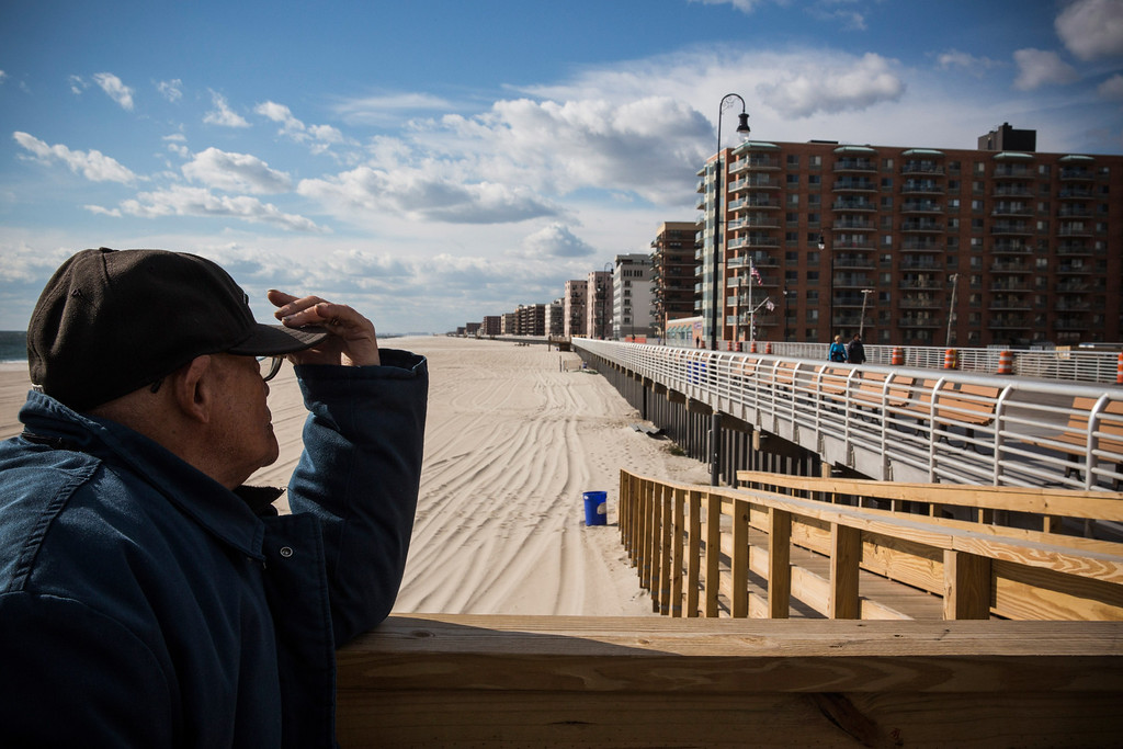 . LONG BEACH, NY - OCTOBER 25:  A man pauses while walking down the Long Beach boardwalk on October 25, 2013 in Long Beach, New York. The Long Beach boardwalk was severely damaged by Superstorm Sandy last year, which killed 285 people and caused billions of dollars in damage, though the boardwalk reopened today. Long Beach\'s new boardwalk is made of Brazilian hardwood and is estimated to have a lifespan of 30-40 year; the previous boardwalk was only scheduled to last  three to seven years.  (Photo by Andrew Burton/Getty Images)