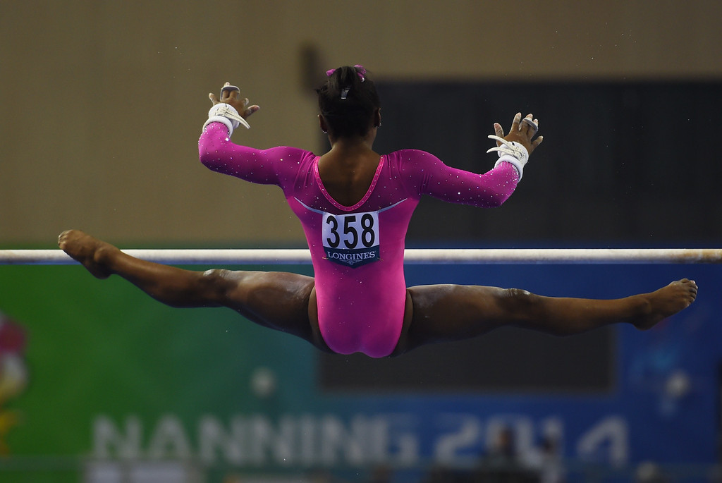 . Simone Biles of the US performs on the uneven bars during the women\'s qualification at the Gymnastics World Championships in Nanning, in China\'s southern Guangxi province on October 5, 2014.GREG BAKER/AFP/Getty Images